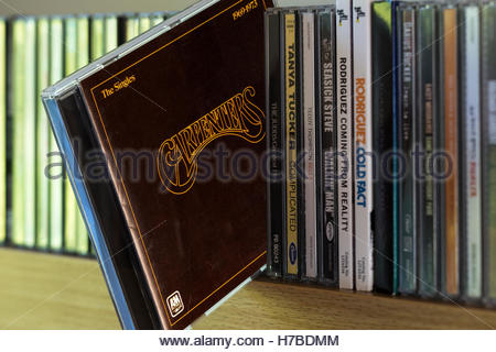 The Carpenters Singles 1969-1973 CD being chosen from a shelf of other CD's - Stock Photo