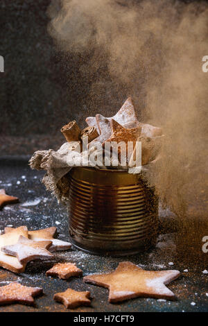 Homemade shortbread star shape sugar cookies with sugar and cinnamon sprinkling powder in old tin can sackcloth - Stock Photo