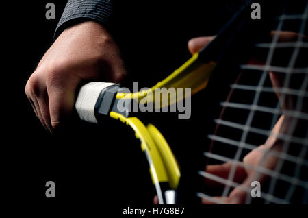 Hand on grip and swinging a tennis racket. Isolated on black background. - Stock Photo