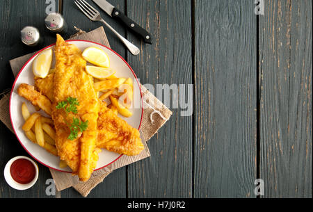 Two pieces of battered fish on a plate with chips on a wooden table with space - Stock Photo