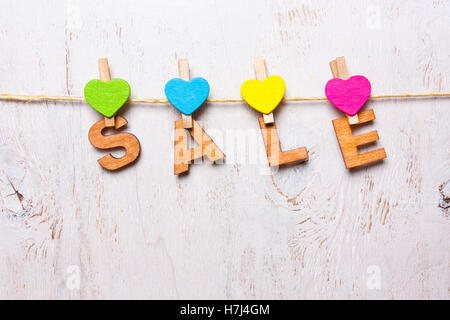 the word 'sale' of wooden letters on a white background - Stock Photo