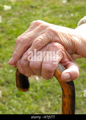 Hands of an old woman on a walking stick - Stock Photo