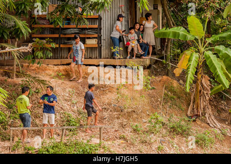 People from houses along the banks of the river watching the Moyog river bamboo rafting festival 2016 Penampang - Stock Photo