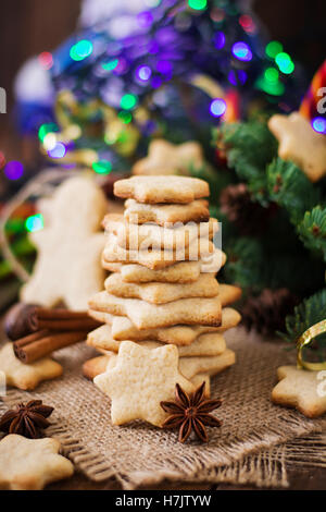 Christmas cookies and tinsel on a dark wooden background - Stock Photo