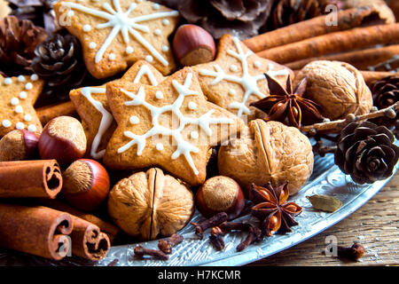 Christmas decor with homemade gingerbread cookies stars, cones, nuts and Christmas spices over rustic wooden background - Stock Photo