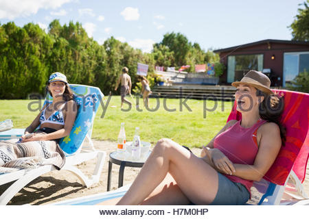 Mother and teenage daughter relaxing on lounge chairs on sunny summer beach - Stock Photo