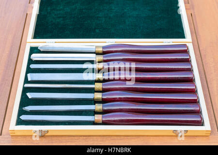 Set of almost new wood turning chisels in wooden box on table - Stock Photo