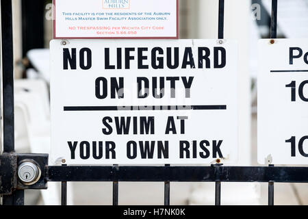 A sign stating no lifeguard on duty, swim at your own risk, for a private swimming pool for a neighborhood association. - Stock Photo