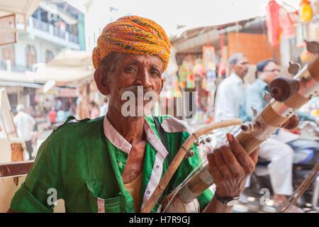 A Rajasthani Indian man playing a Ravanahatha a traditional musical instrument, Pushkar, India - Stock Photo