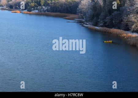 Man fishing on a small yellow boat near shoreline. A cold day on November. - Stock Photo