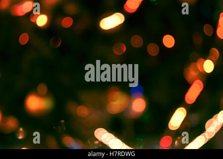 Christmas lights background. Blurred electric garland on Christmas tree. Red, green, yellow, orange, blue glow - Stock Photo