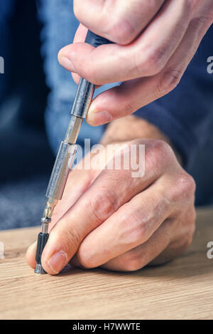 Man assembling furniture at home on the floor, hand with screwdriver - Stock Photo