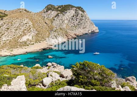 Azure bay, azure bay with crystal clear waters, towering above the bay mountains on either side, a riot of greenery - Stock Photo