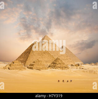 Dramatic sunset behind all distant Egyptian Pyramids together with line of camels walking in foreground in Giza, - Stock Photo