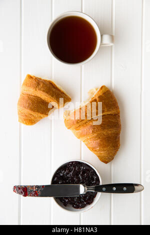 Tasty buttery croissant, cup of black tea and jam in jar. Top view. - Stock Photo