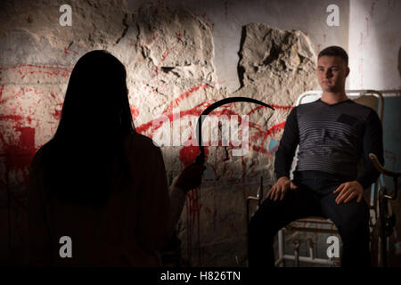 Shadowy female figure holding large iron sickle in front of patient near blood stained wall for concept about murder - Stock Photo