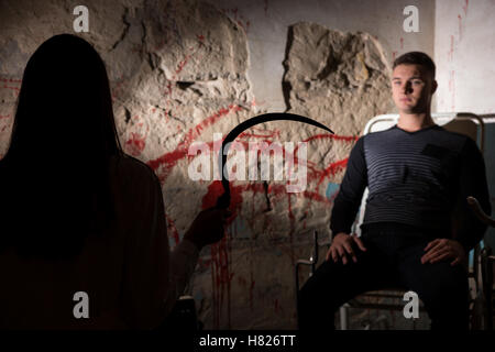 Shadowy female figure holding iron sickle in front of patient near blood stained wall for concept about murder and - Stock Photo