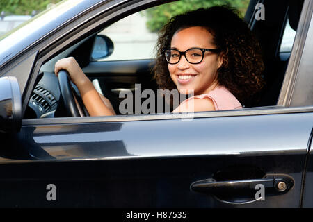 Happy young woman seated in her new car - Stock Photo