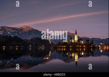 Chapel on a small island at twilight reflected in calm water, Bled lake in Slovenia - Stock Photo