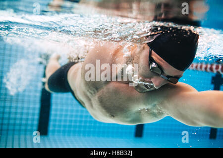 Professional male swimmer practising in swimming pool. Underwater shot of young sportsman swimming in pool. - Stock Photo