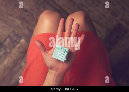 Top view woman with red dress holding a small blue gift box in her hand - Stock Photo
