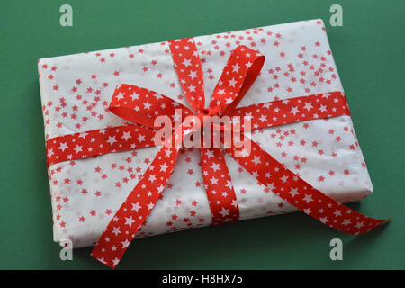 Christmas present, beautifully wrapped and decorated with a red ribbon - Stock Photo