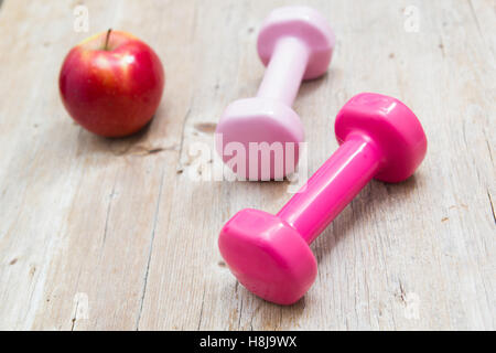 Weights and fruit on wooden background healthy living concept - Stock Photo