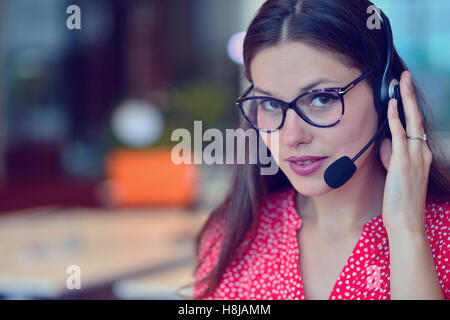 Young woman working in call centre - Stock Photo