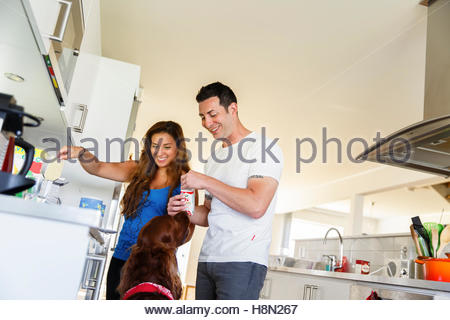 Couple feeding dog in kitchen - Stock Photo