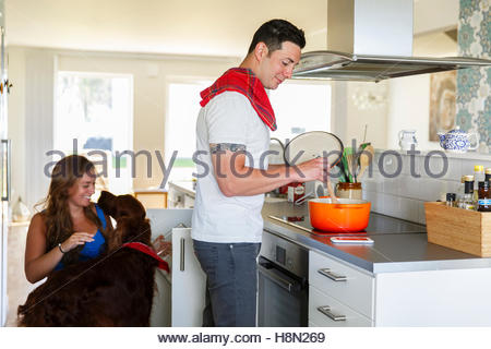 Man cooking and woman playing with dog in kitchen - Stock Photo