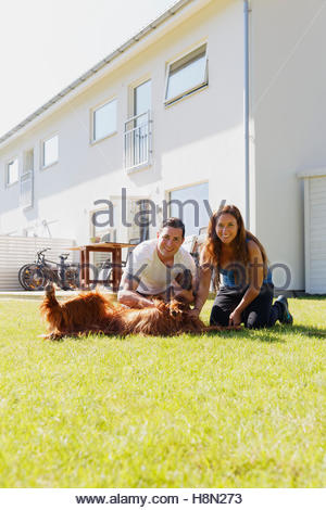 Portrait of couple with dog in back yard - Stock Photo