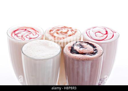 five glasses of various milkshakes chocolate, strawberry and vanilla isolated on white background - Stock Photo
