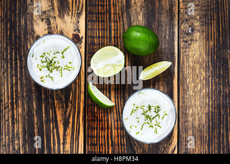 Raw  lime cheesecake in a glass on wooden table viewed from above. Rustic background with free text space - Stock Photo