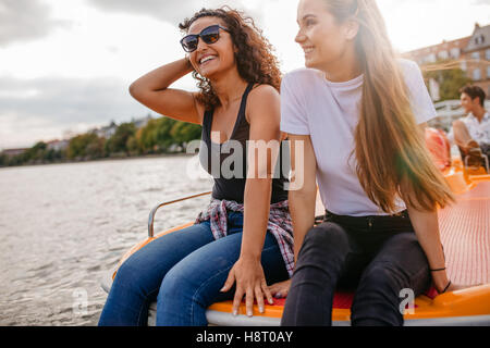 Outdoors shot of two female friends sitting in front pedal boat. Teenage friends relaxing on pedal boat in lake - Stock Photo