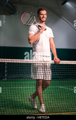 Professional delighted tennis player holding racket - Stock Photo