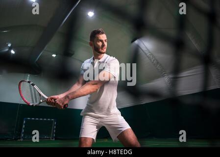 Professional serious man playing tennis - Stock Photo