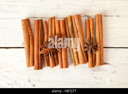 Cinnamon sticks and star anise on rustic white wooden table, high angle view - Stock Photo