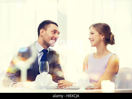 smiling couple looking at each other at restaurant - Stock Photo