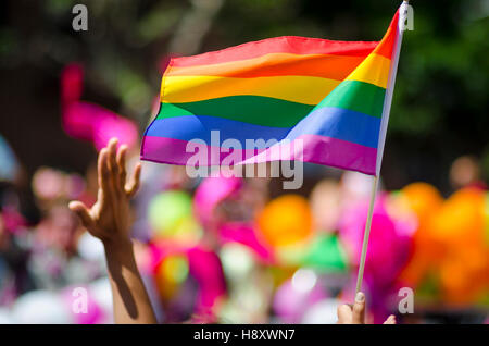 A supporting hand waves in front of a rainbow flag flying on the sidelines of a summer gay pride parade - Stock Photo