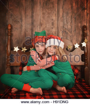 Little children wearing pajamas with Christmas hats hugging each other on a bed for a family at home concept or - Stock Photo