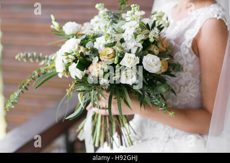 Bridal bouquet. The bride's . Beautiful of white flowers and greenery, decorated with silk ribbon, lies on vintage - Stock Photo