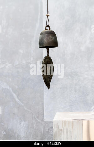 Bronze leaf of a wind bell hanging outdoor. Wind bells can generally be found in buddhist temple, it makes sound - Stock Photo