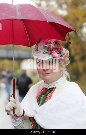 Haworth, UK. 19th Nov, 2016. A women wearing Victorian clothing stood under a red umbrella, Haworth, 19th November - Stock Photo