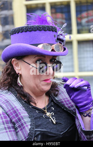 Haworth, UK. 19th Nov, 2016. A women in a purple Steampunk outfit with an electronic cigarette, Haworth, 19th November - Stock Photo
