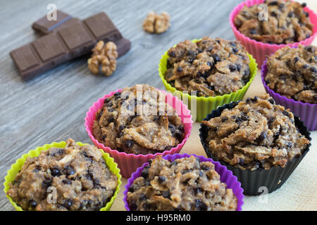 Fruit muffins on a yellow napkin and a grey wooden table. Walnuts and chocolate in the background. - Stock Photo