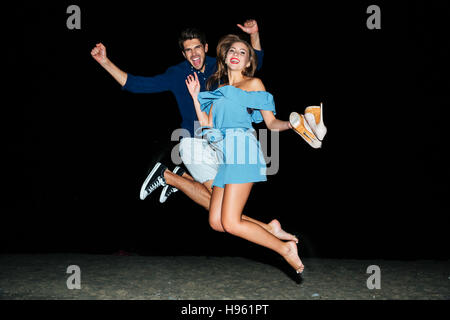 Happy young couple jumping in the air on the beach at night - Stock Photo