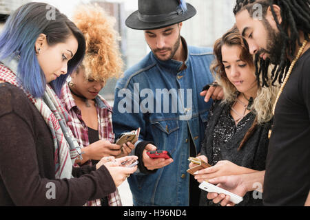 Young people outdoors using smartphones - Stock Photo