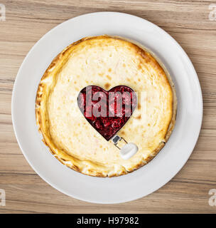 Delicious round cheesecake with raspberry heart on the white plate. Sweet food. - Stock Photo
