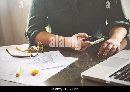 Architect woman working at computer and calling her client - Stock Photo