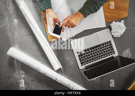 Top view of architect woman working at computer and calling her client - Stock Photo